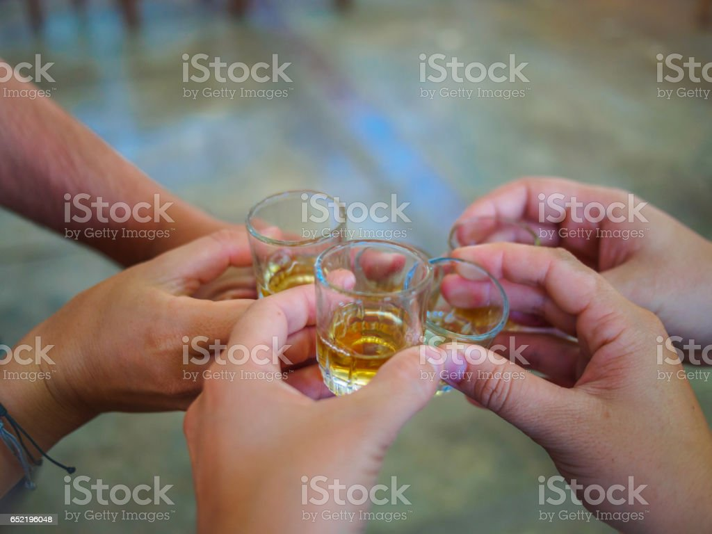 Five human hands toasting with pisco stock photo