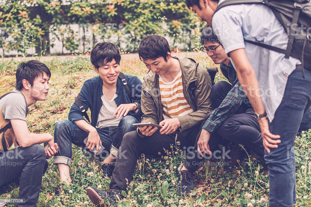 Five Japanese Students Using Digital Tablet, Campus Park, Kyoto, Japan stock photo
