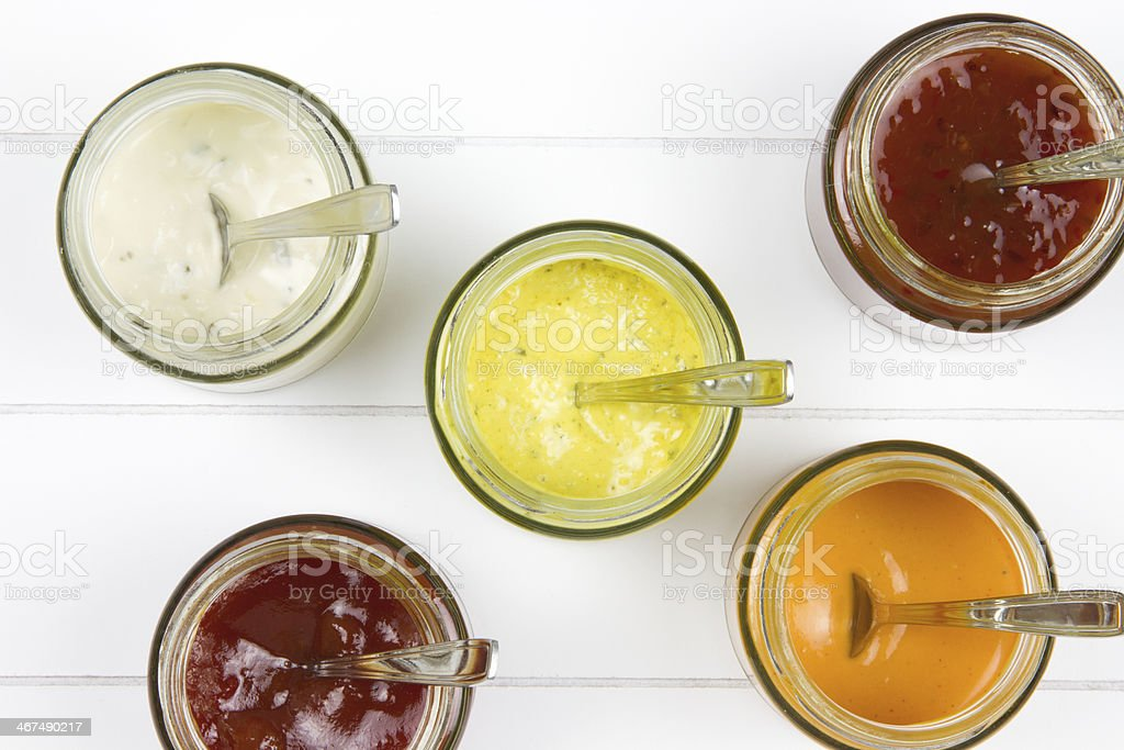 five jars filled with all kind of sauces stock photo