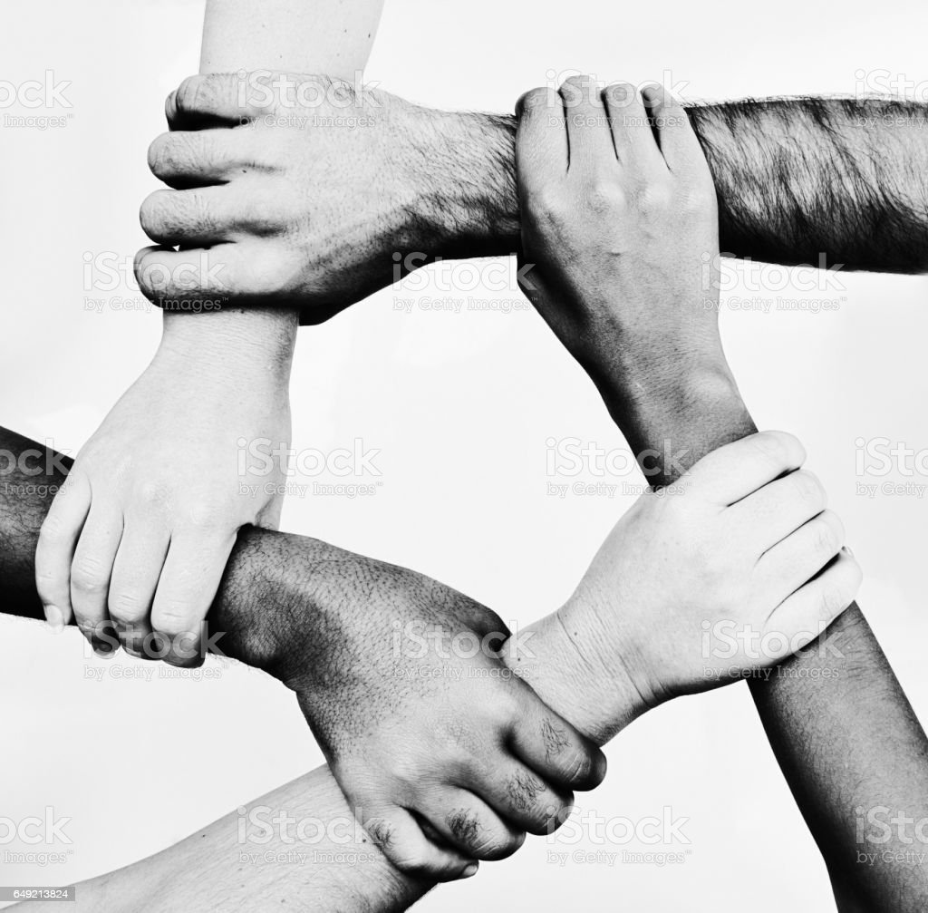 Five mixed hands clasped in unity: black-and-white image stock photo