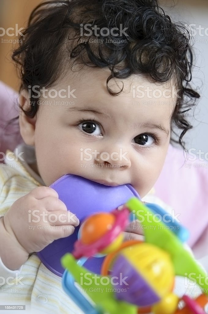 Five Months Old Infant With Colourful Toys In Her Mouth royalty-free stock photo