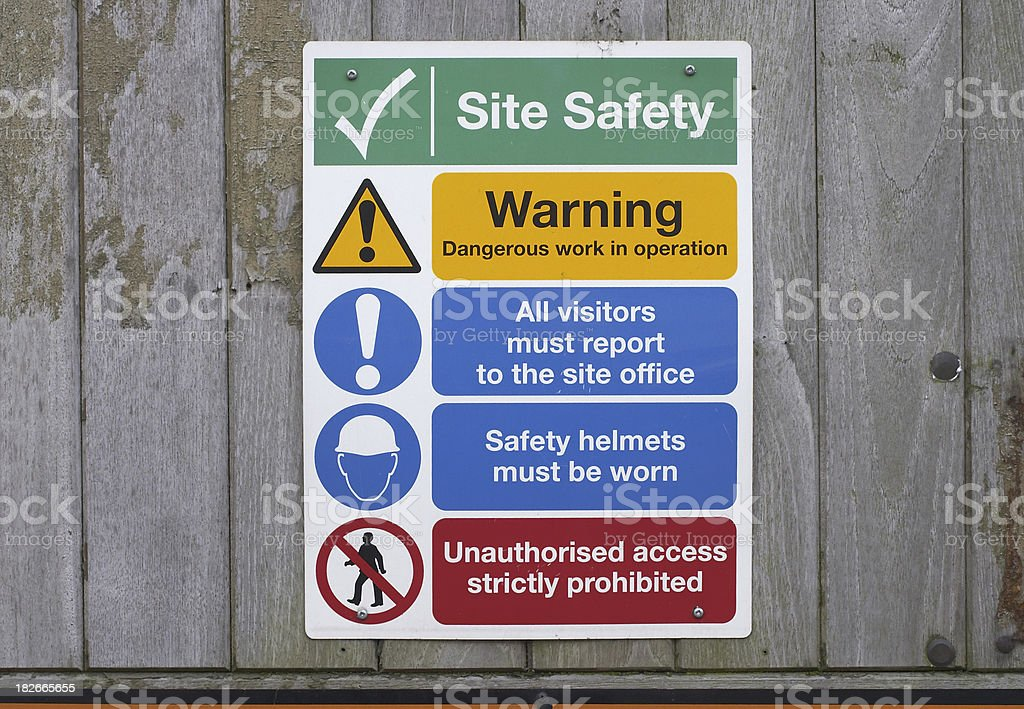 Construction site safety notices on wooden fence stock photo
