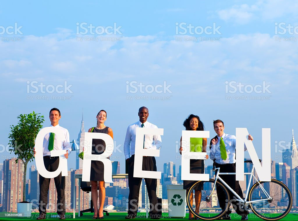 Five office workers holding a sign that spells green stock photo