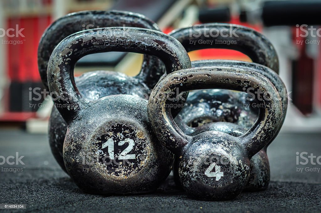 Five old and rusty Kettle Bells on the floor. stock photo