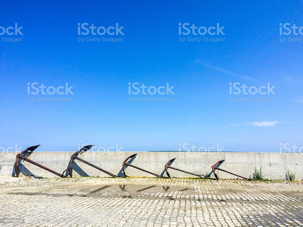 Five old decorative anchors standing in row at sea port stock photo