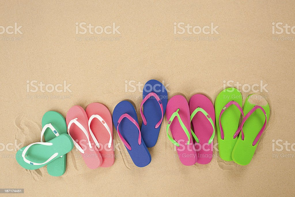 Five pair of flip flop isolated on sand. royalty-free stock photo
