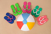 Five pairs of flip flop and beach ball.