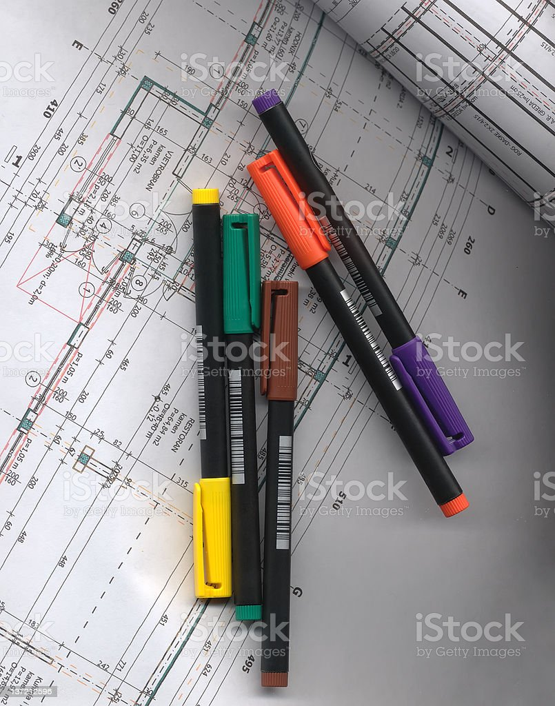 Five pens lay on the open building-plan royalty-free stock photo