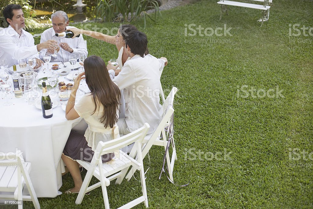 Five people at outdoor party socially drinking stock photo