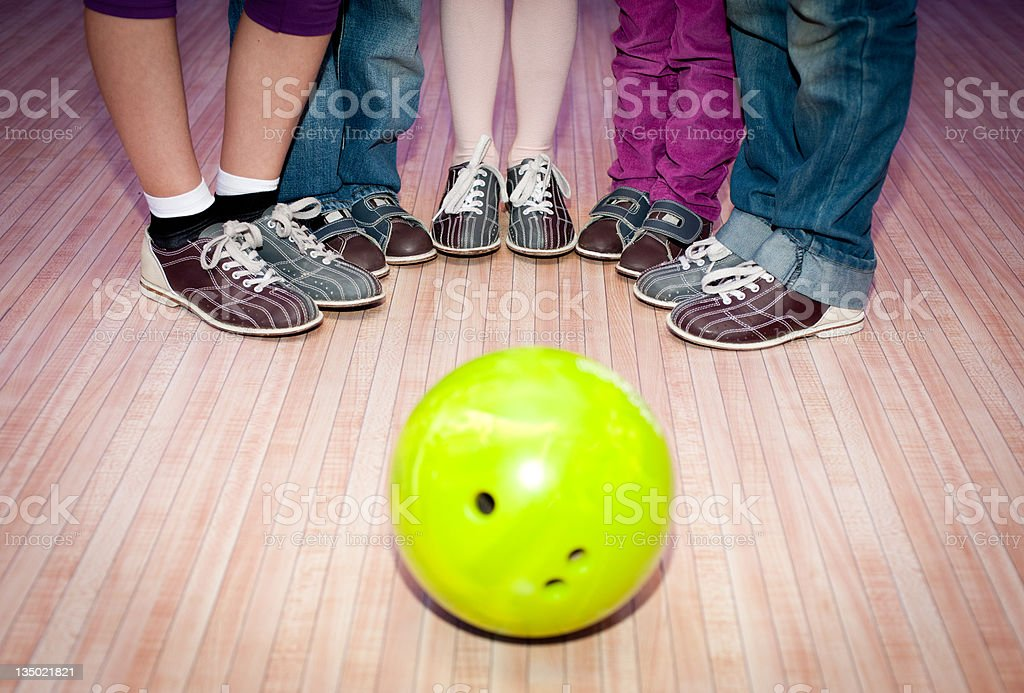 Five people surrounding a bright yellow bowling ball stock photo