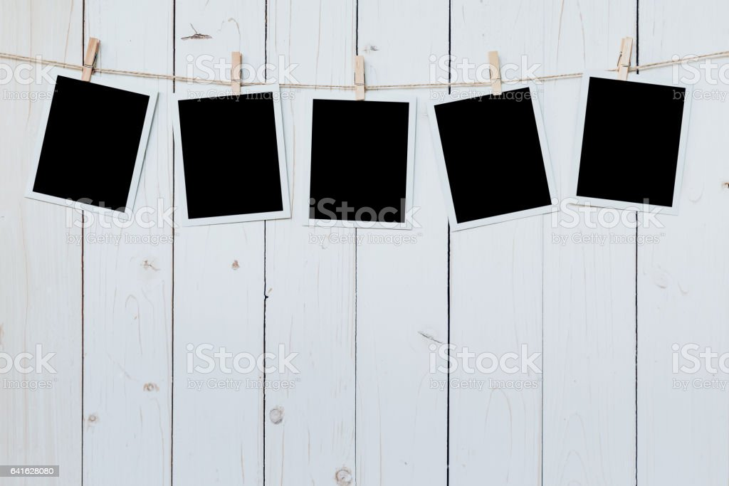 five photo frame blank hanging on wooden board background. stock photo