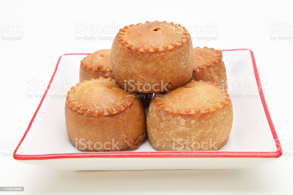 five pork pies on white plate with plain background stock photo