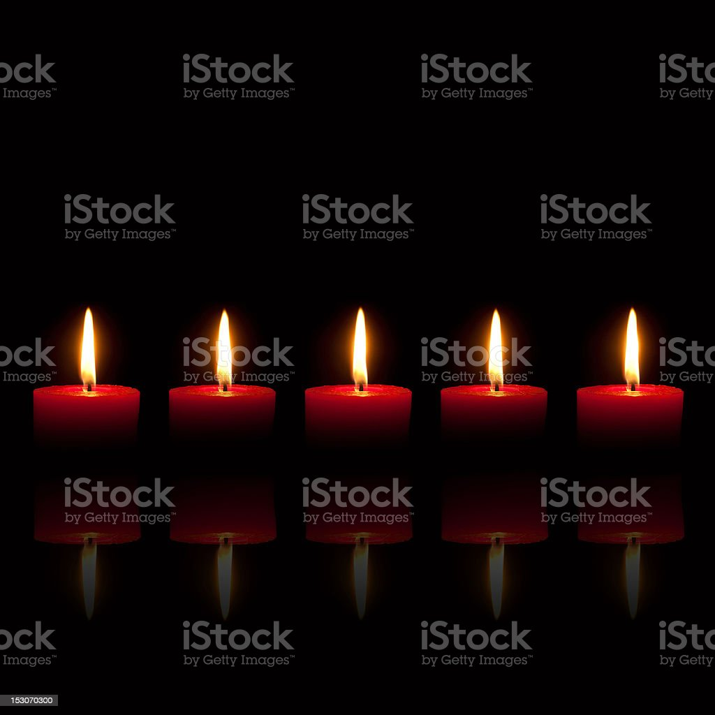 Five red candles burning in front of black background royalty-free stock photo