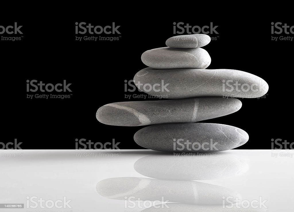 Five round stones piled up on a white surface royalty-free stock photo
