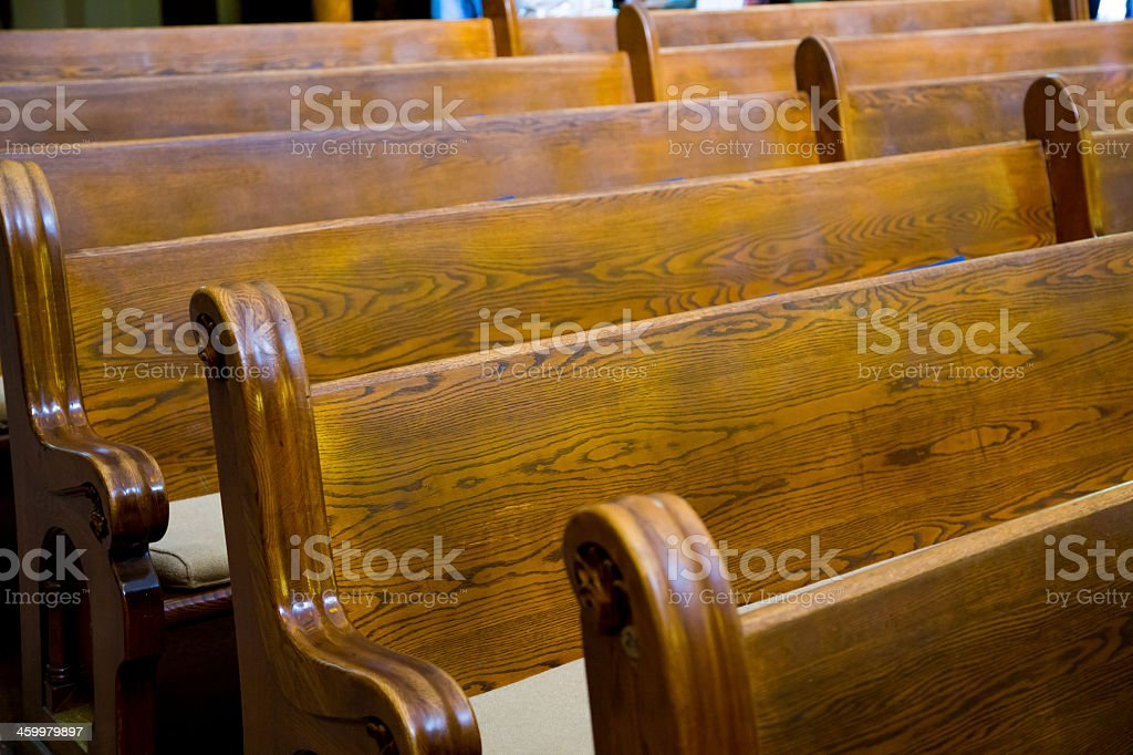 Five rows of old, wooden church pews stock photo