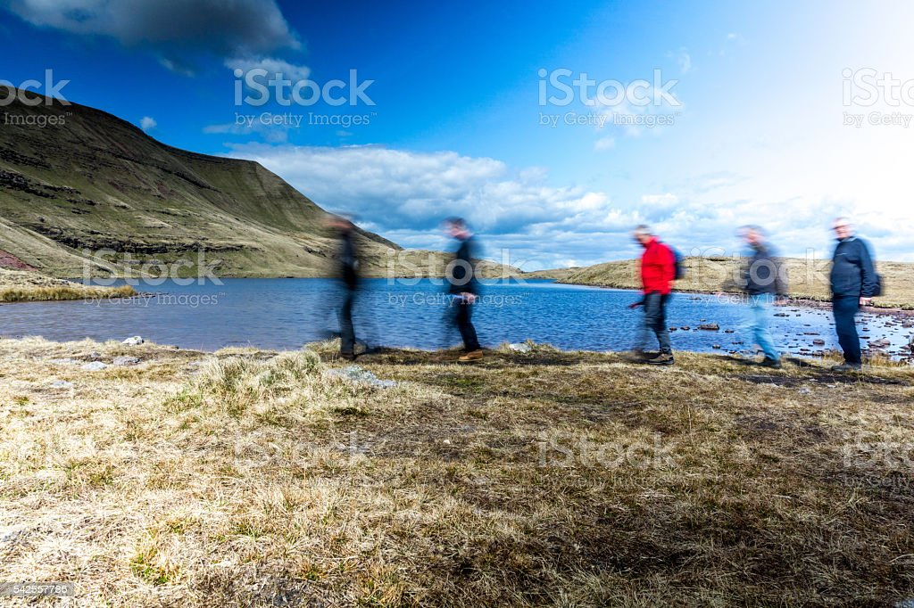 Five seniors blur walking quickly in Welsh countryside stock photo