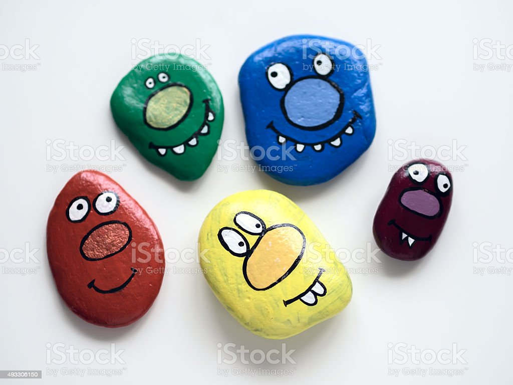 Five smiling faces of monsters. Painted acrylic pebbles. stock photo