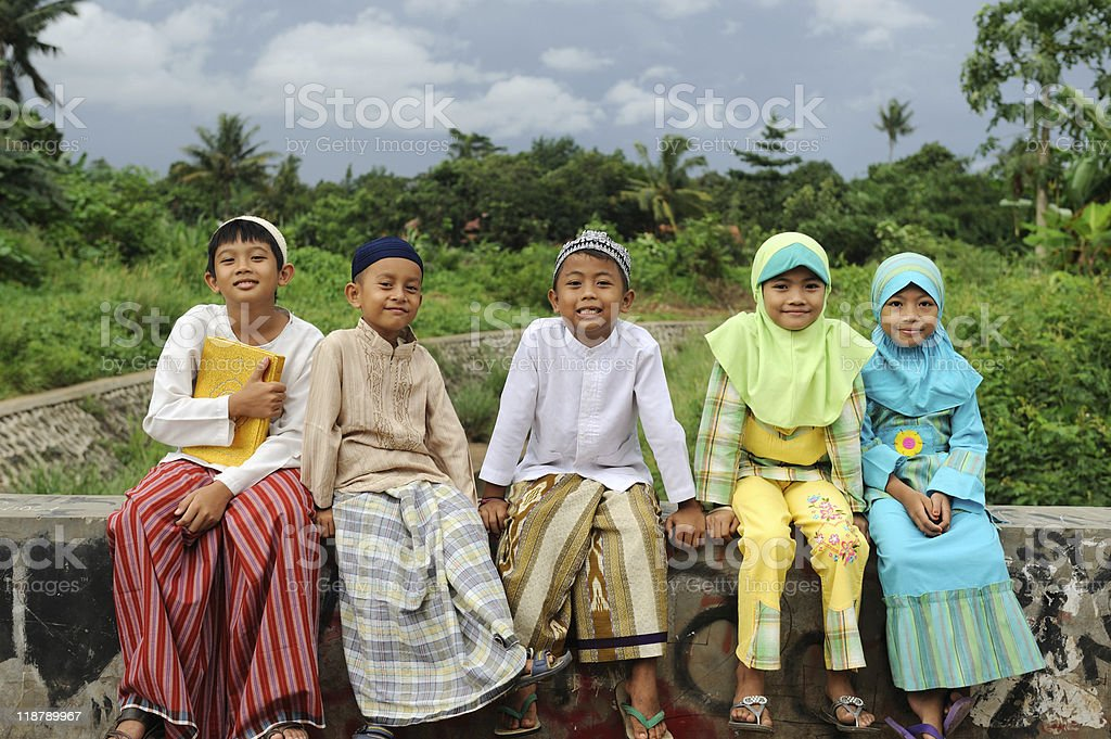Five smiling young Muslim kids sitting on a brick wall royalty-free stock photo