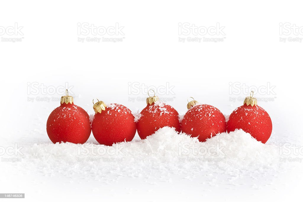 Five spherical red Christmas ornaments nestled in snow pile royalty-free stock photo