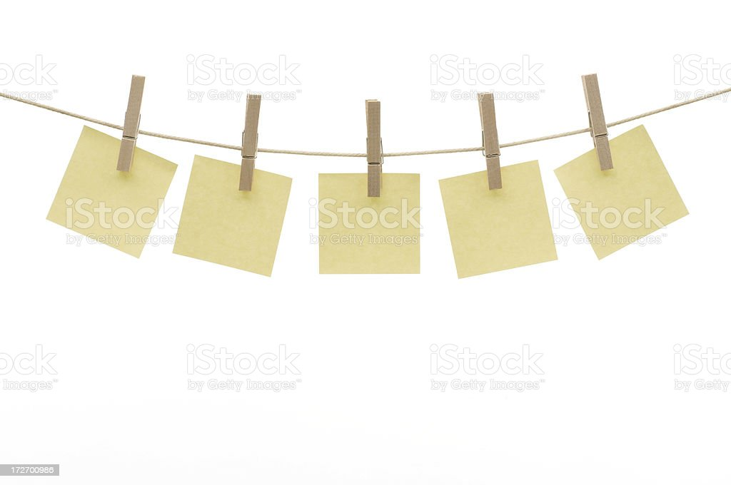 Five square yellow blank notes hanging by clothespins on clothesline stock photo