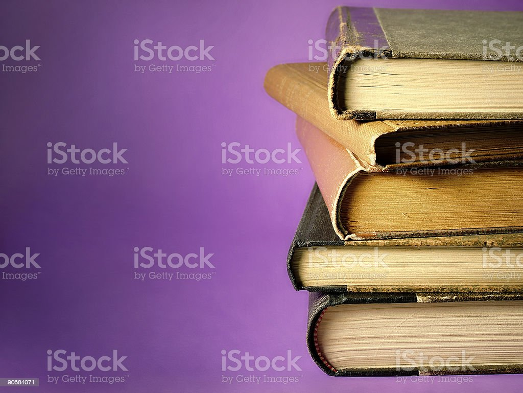 Five stacked vintage books against a purple background royalty-free stock photo