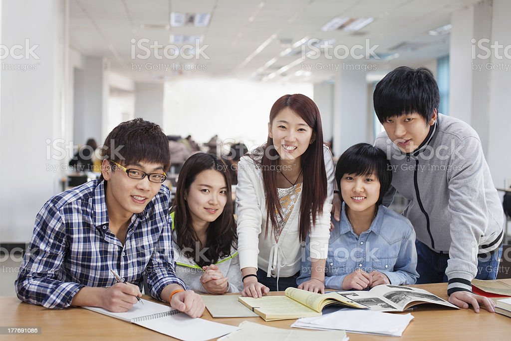 Five students at a table with books and notebooks stock photo