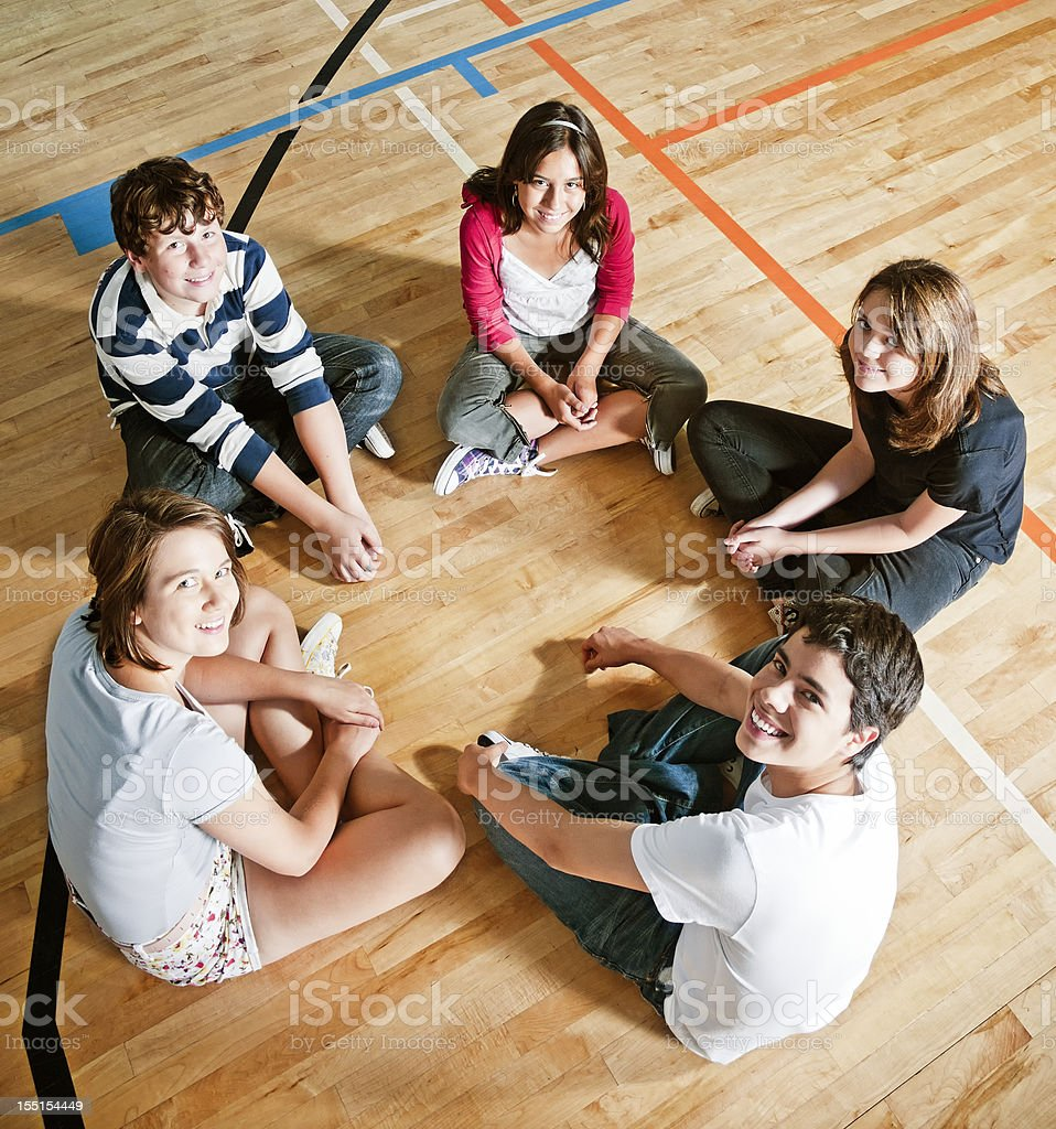 Five students sitting in a circle in a gym stock photo