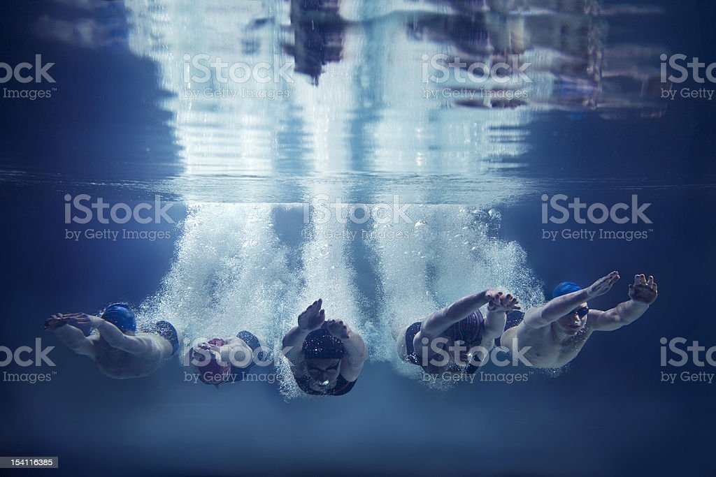Five swimmers jumping together into water- underwater stock photo