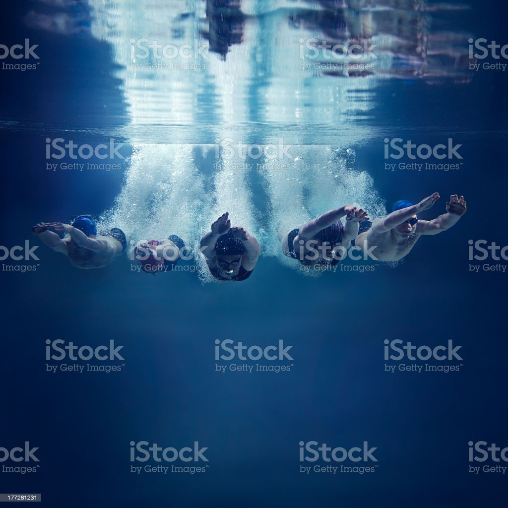 Five swimmers jumping together into water, underwater view stock photo