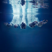 Five swimmers jumping together into water, underwater view