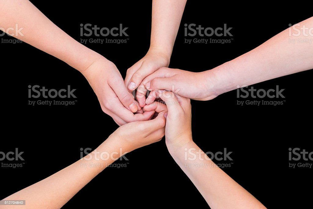 Five teenage arms with hands entangled isolated on black backgro stock photo