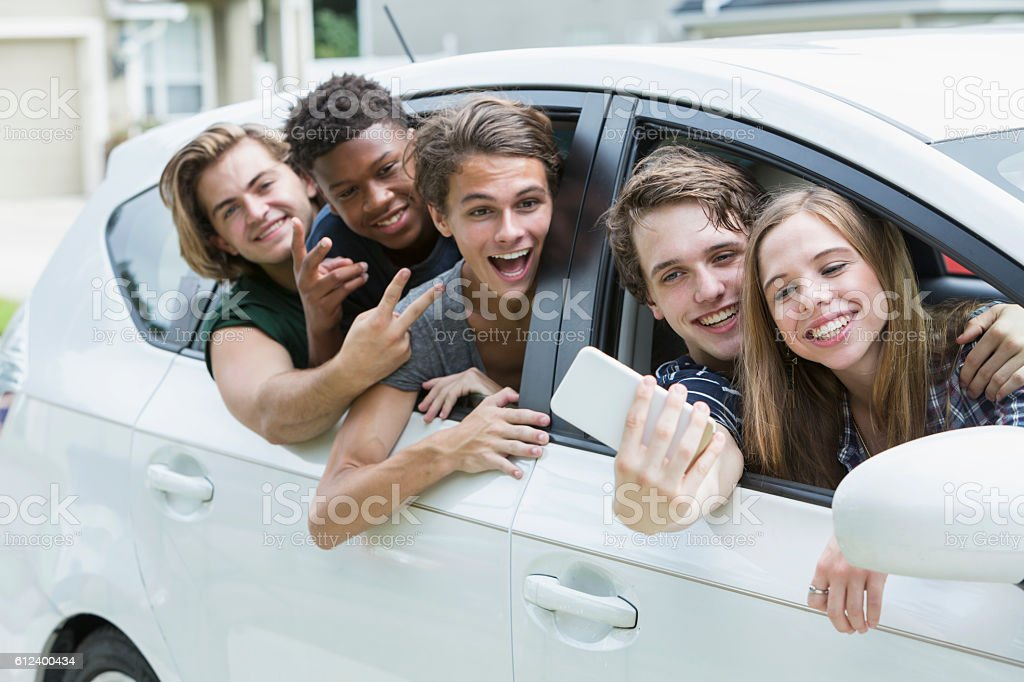 Five teenage friends taking selfie in a car stock photo