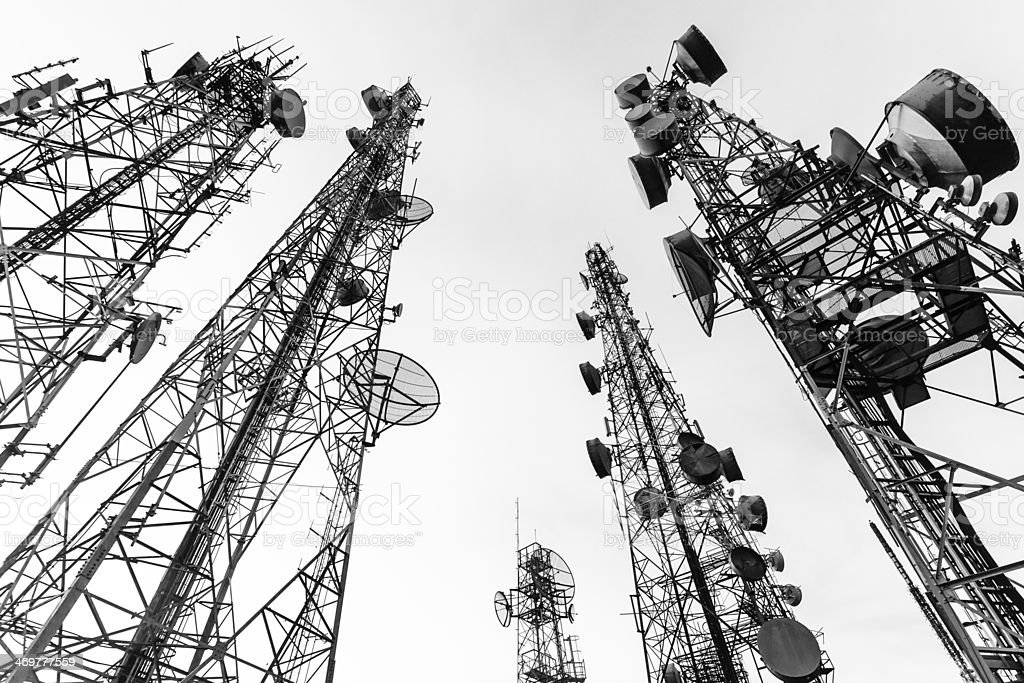 Five telecommunication towers from the ground at their bases stock photo