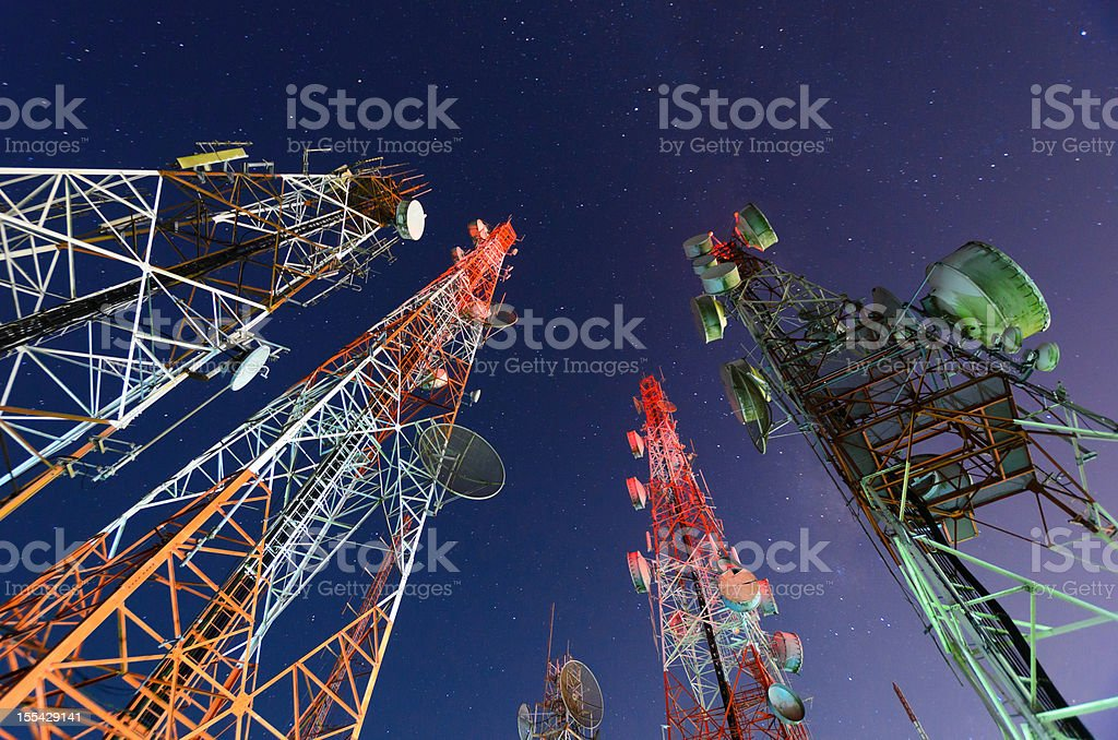 Five telecommunication towers under a night sky  stock photo