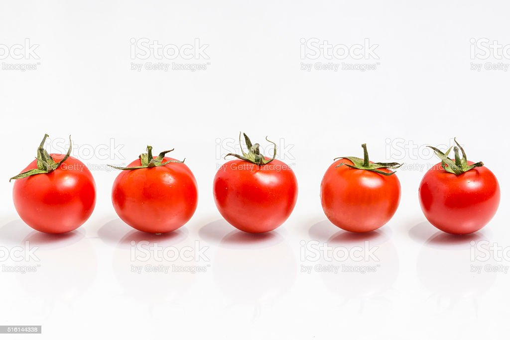 Five tomatoes in a row  isolated on white stock photo