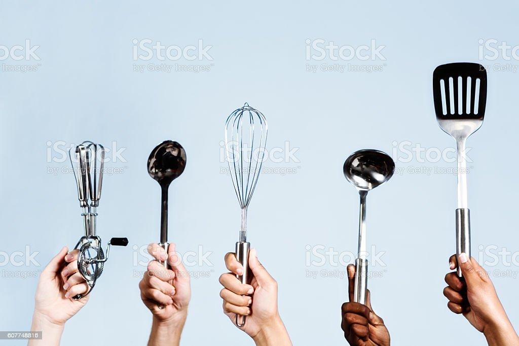 Five wannabe chefs hold up their kitchen utensils stock photo