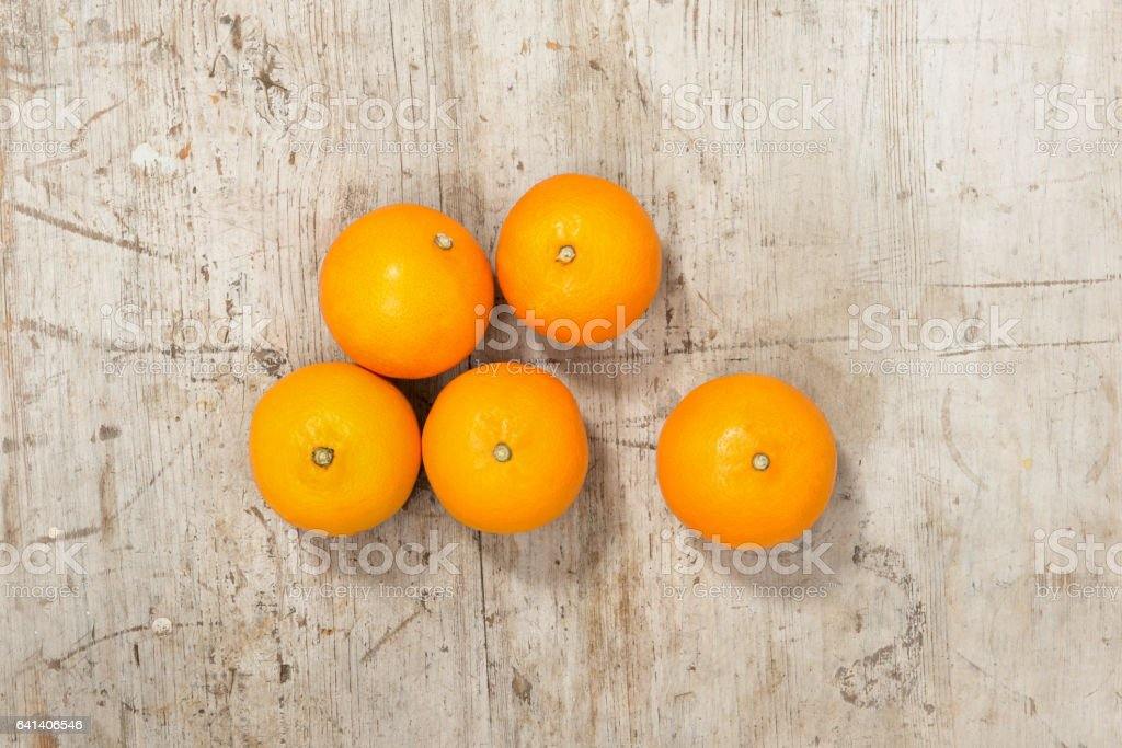 Five Whole Oranges on a Wooden Surface stock photo