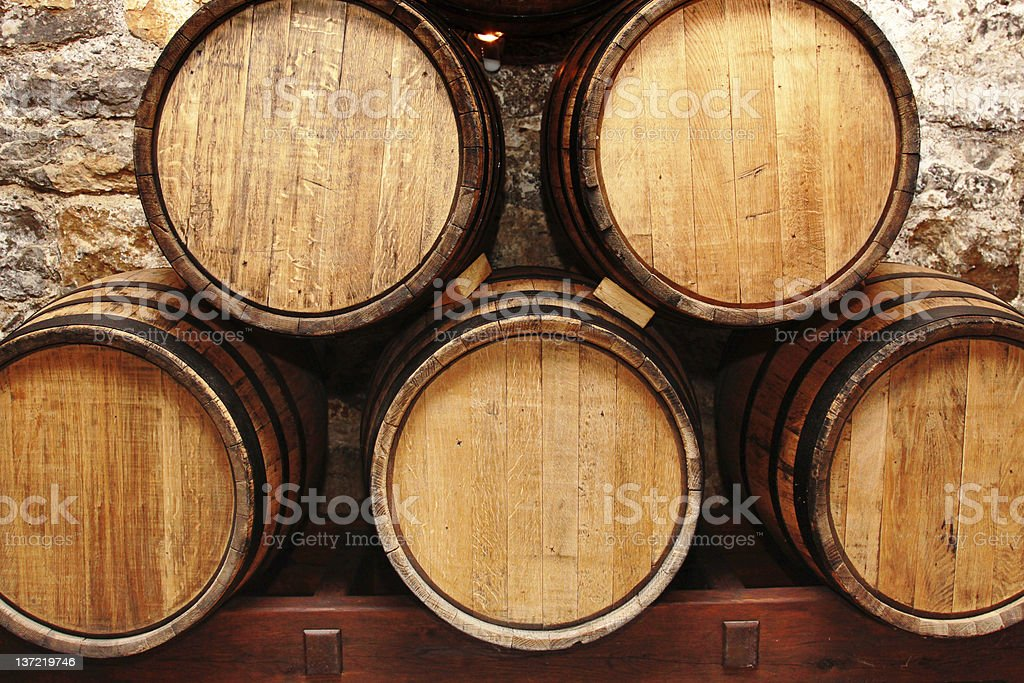 Five wine barrels stacked together in a cellar stock photo