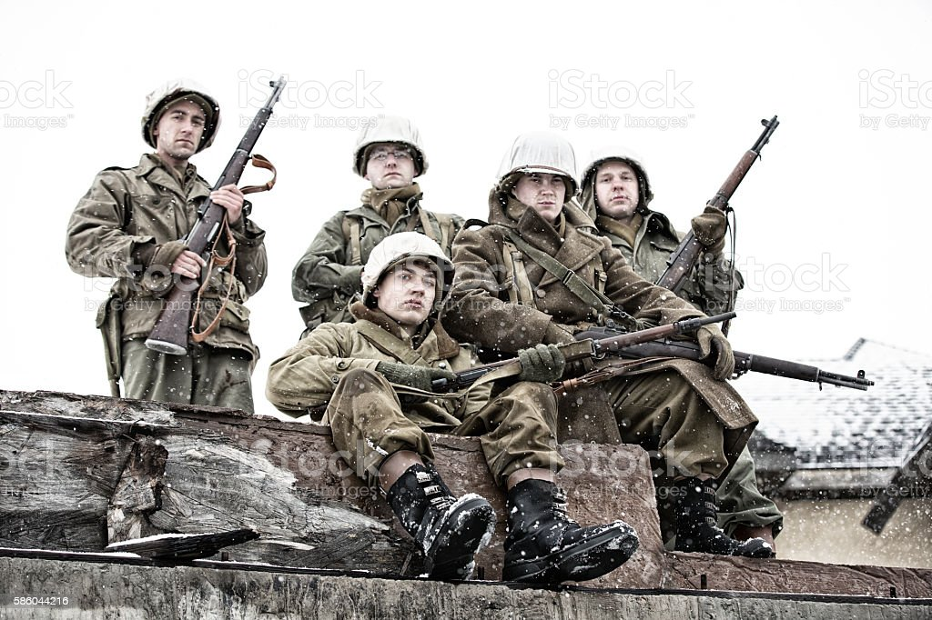 Five WWII Soldiers Resting on Bombed Building stock photo