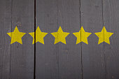 Five yellow ranking stars on black wooden background