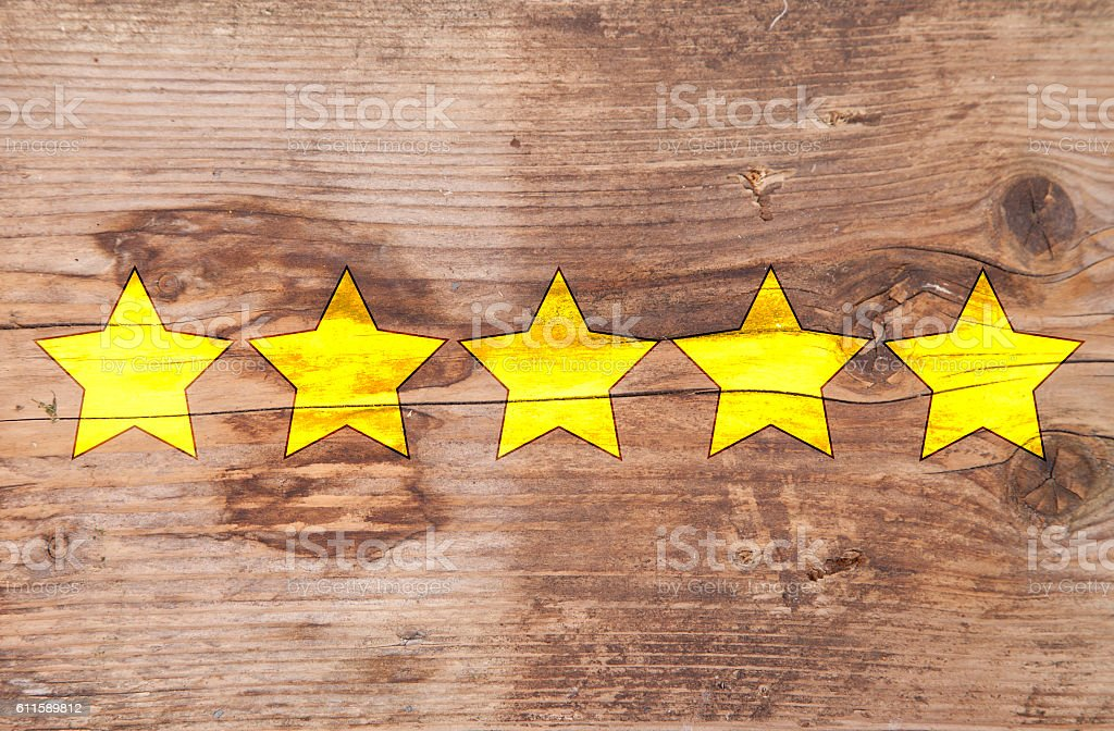 Five yellow ranking stars on wooden background stock photo