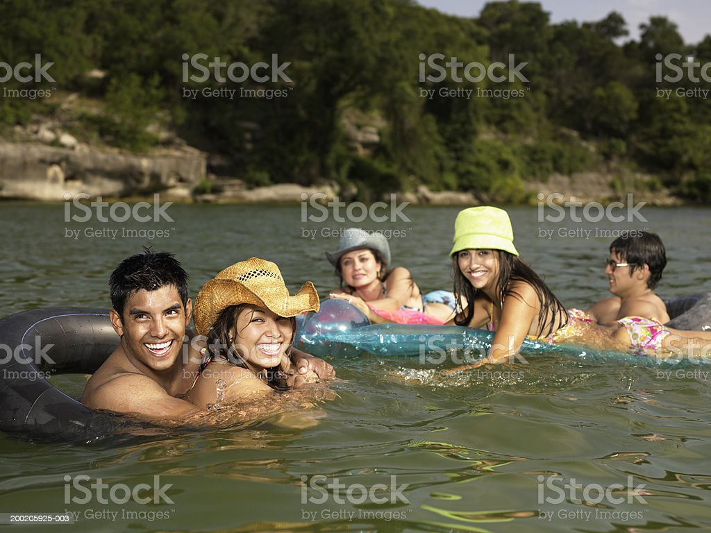 Five young adults on inner tubes and rafts in lake, smiling royalty-free stock photo
