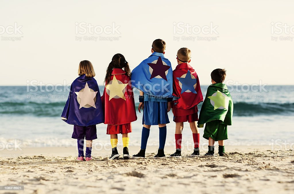Five Young Children Dressed as Superheroes on Beach stock photo