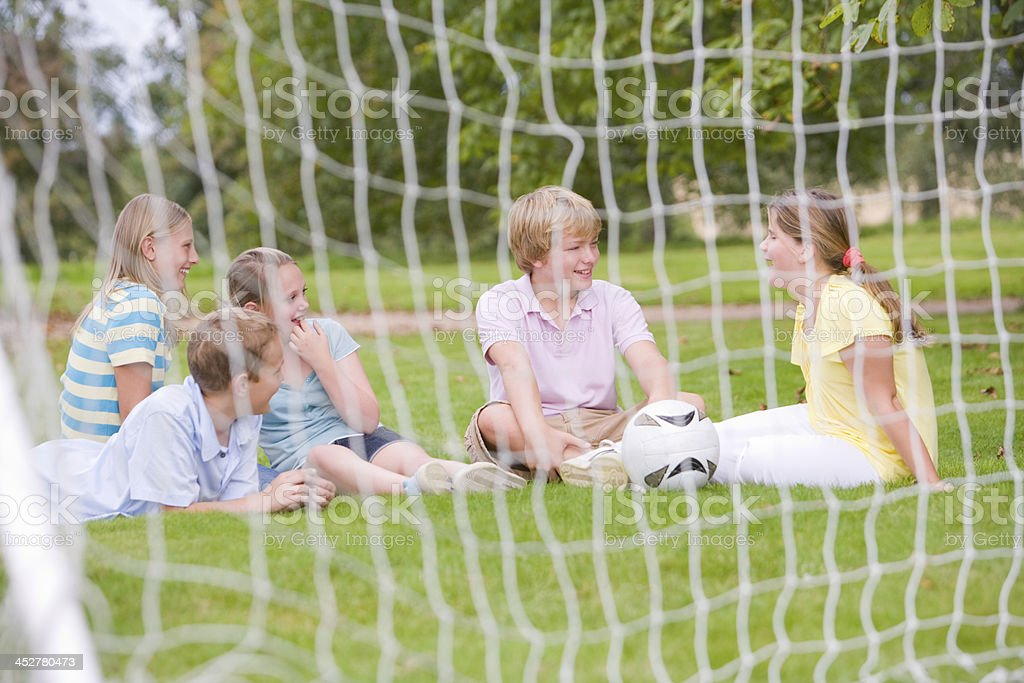 Five young friends on soccer field talking and smiling royalty-free stock photo
