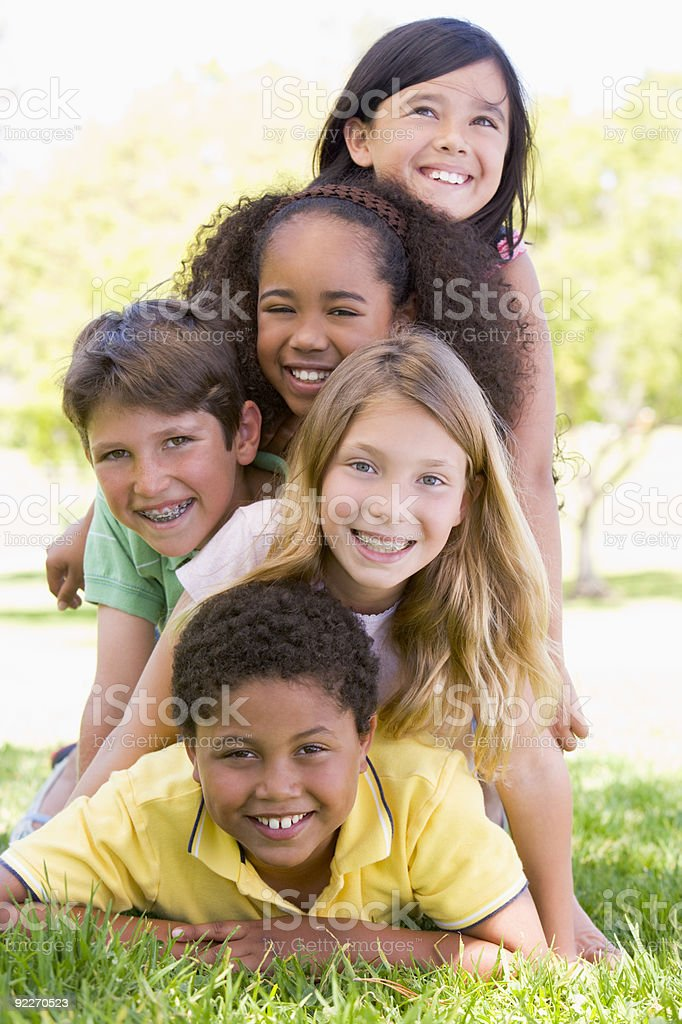 Five young friends piled up stock photo