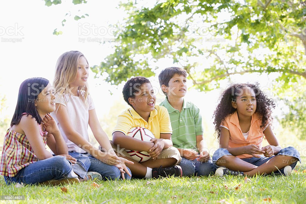 Five young friends sitting outdoors with soccer ball royalty-free stock photo
