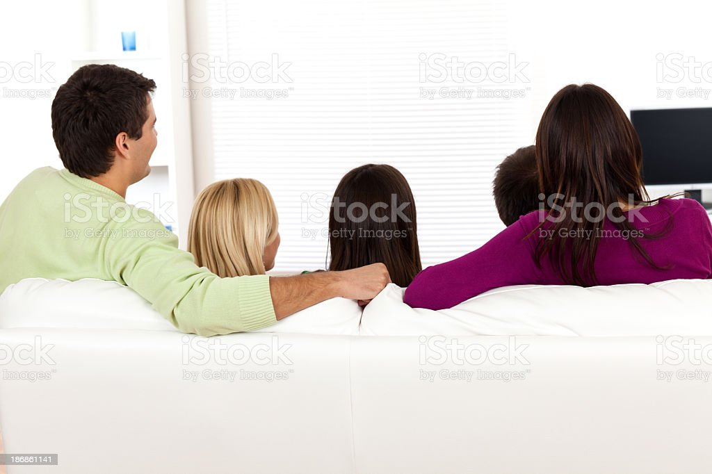 Five young friends watching television royalty-free stock photo