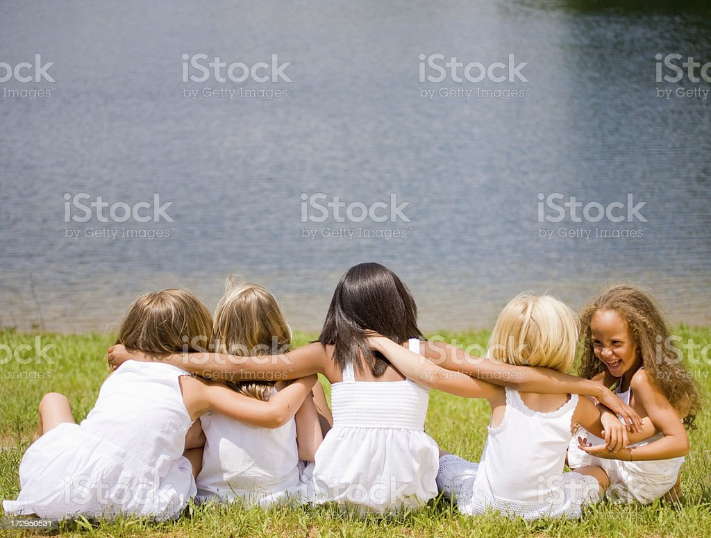 Five young girls in white sitting by a lake royalty-free stock photo
