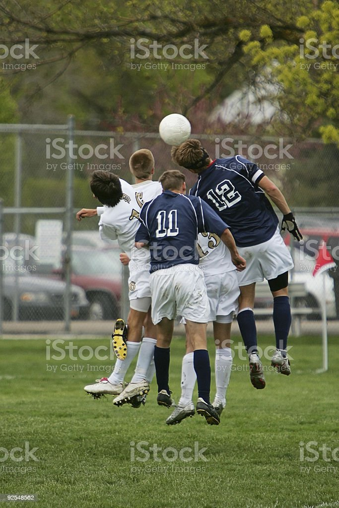 Five Young Male Soccer Players Jump to Head Ball stock photo