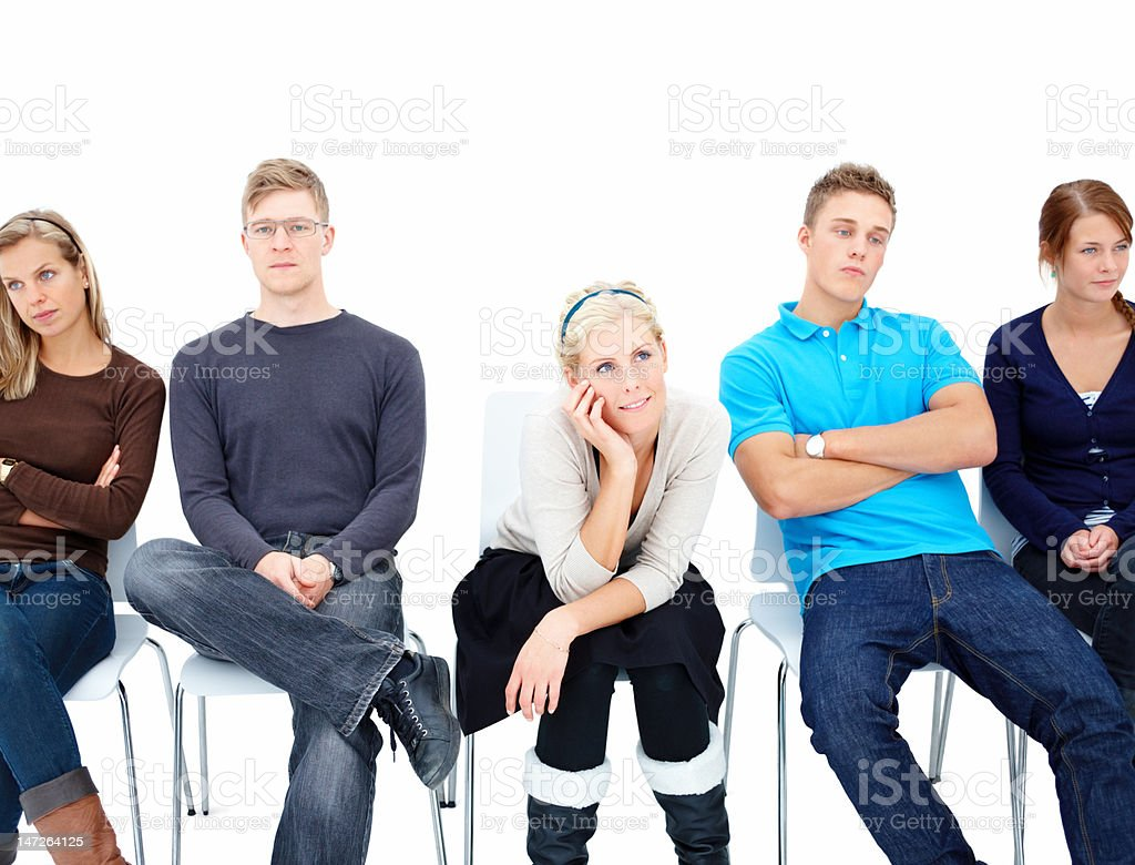 Five young men and women sitting in a line royalty-free stock photo